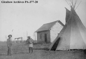 Title: Cabin and tipi at Lac Ste. Anne, Alberta. Date: 1896 Remarks: George Wilkins, left. Credit: Glenbow Museum (Image No: PA-377-20)